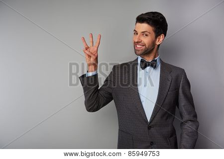 Smiling man showing three fingers and looking at camera
