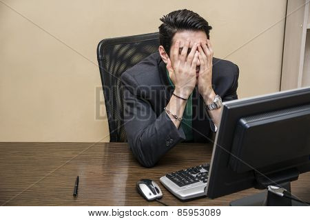 Desperate, Worried Young Businessman Sitting At His Desk