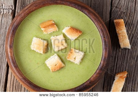 Tasty spinach green cream soup in a bowl with croutons