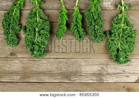 Kale leaves over a wooden background