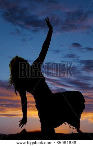 Silhouette Of A Woman In A Skirt Kneel Hand Up