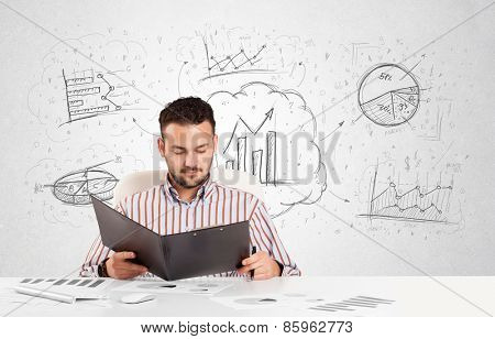 Business man sitting at white table with hand drawn graph charts