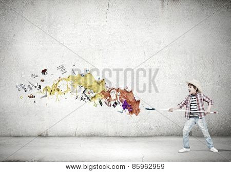Boy of school age painting wall with brush