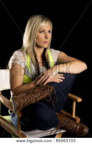 Woman Sitting Crossed Legged In A White Chair On Black