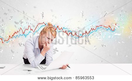 Business woman sitting at table with stock market graph 3d letters