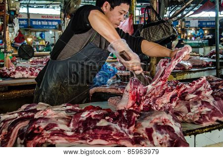 Butcher cuts up beef in an open air market in Vietnam