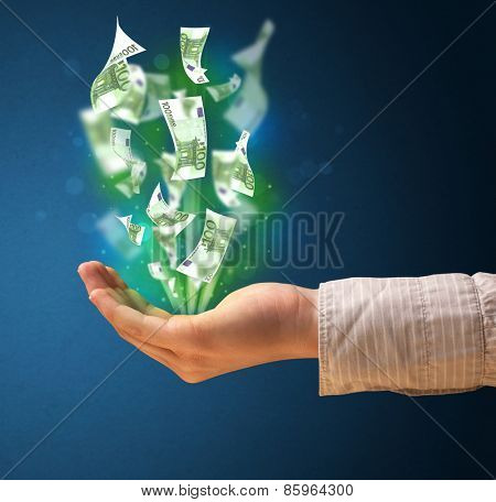Woman holding glowing paper moneys in her hand