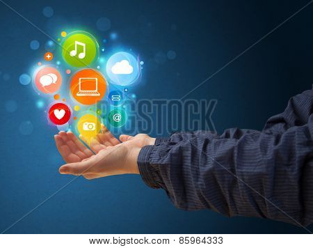Young woman holding colorful multimedia icons in her hand