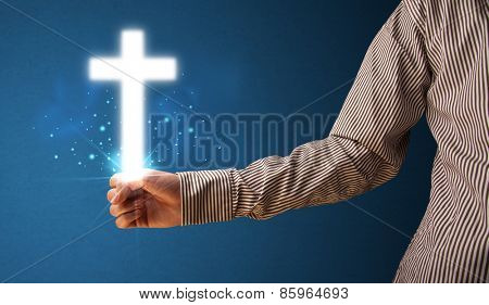 Young businessman holding a glowing cross in his hand
