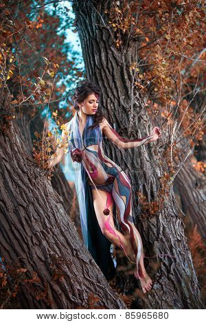 Beautiful Woman In Bodyart On The Autumn Forest Background