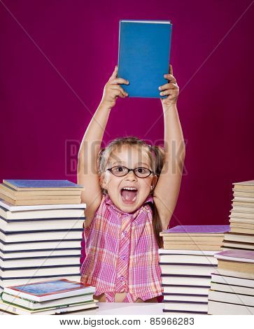 Little scholar girl with pile of books - learning concept
