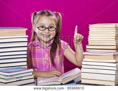 Little scholar girl with pile of books with finger up
