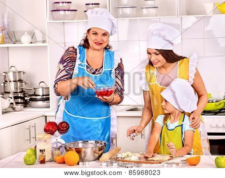 Mature woman with family preparing  dinner at kitchen.