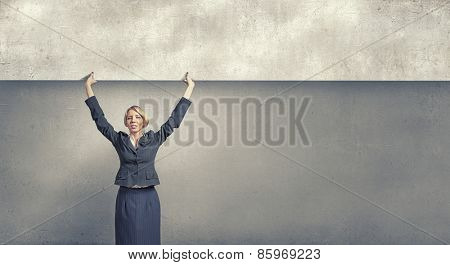 Young businesswoman lifting cement banner above head