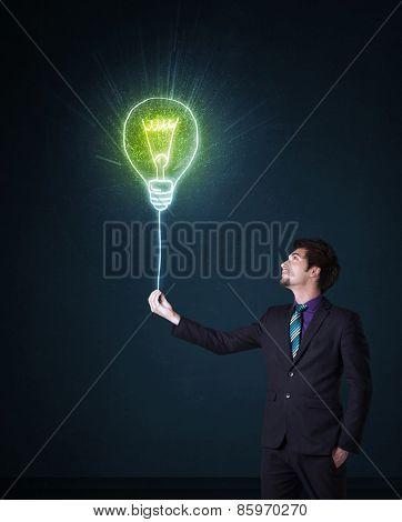 Businessman hold a shining idea bulb on a blue background