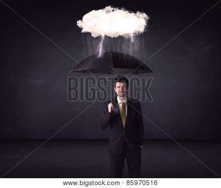 Businessman standing with umbrella and little storm cloud concept on background