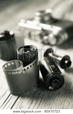 Old Photo Film Rolls, Cassette And Retro Camera On Background. Black And White Stylized.