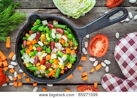 Mixed Vegetables In Vintage Frying Pan, Pot Holder And Ingredients On Wooden Rustic Table.