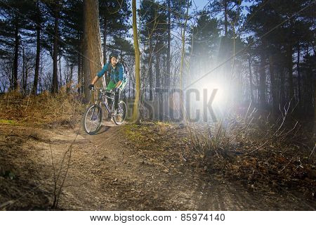 Mountain biker riding his bike on a gravel dirt trail, with the sun in his back at dusk