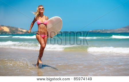 Blonde woman in swimsuit running on the beach with surfboard