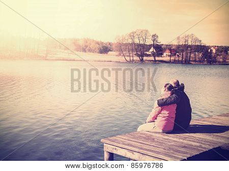 Retro Filtered Photo Of A Couple Sitting On Pier.