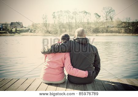 Cuple Sitting On A Pier, Sepia Stylized Picture.