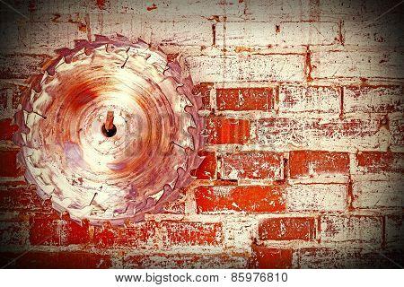 Circular Saw Blade On A Grungy Brick Wall.