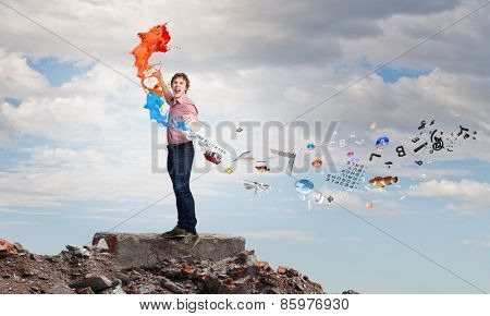 Young emotional man and colorful paint splashes