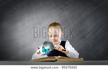 Little school girl examining butterfly with magnifying glass