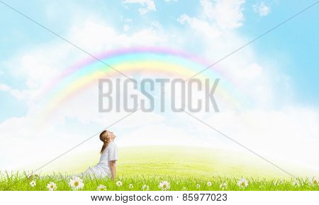 Young smiling girl doing yoga elements on grass
