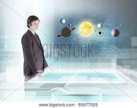 Young businessman looking on table and planets of space spinning around