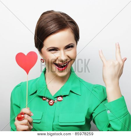 Young happy woman holding red  paper heart and ready for party