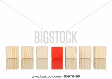 wooden blocks standing in line with red one in the centre