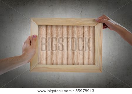 Close up of hands holding wooden blank frame. Place for text