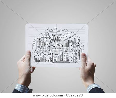 Close up of businessman hands holding opened notepad with sketches