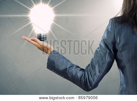 Rear view of businesswoman holding bulb in palm