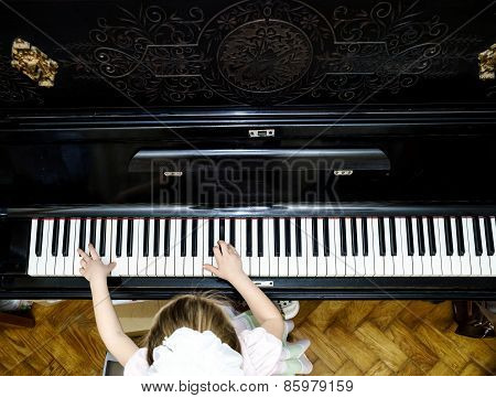 Girl's Hands And Piano Keyboard Close-up View