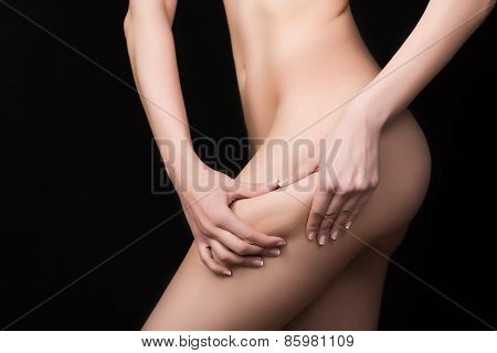 Fit sexy woman holding showing cellulite area.Woman pinches her thigh to control cellulite