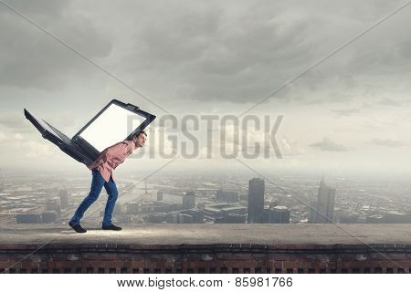 Young man in casual carrying laptop on back