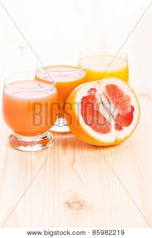 Three Glasses Of Juice With Cut In Half Grapefruit