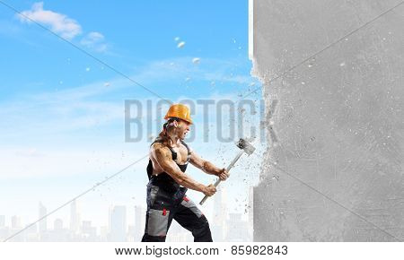 Strong man in uniform breaking wall with hammer