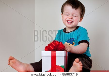 Happy toddler boy opening gift box