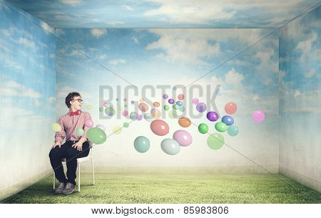 Young funny teenager guy sitting in chair