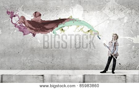 Cute girl of school age painting wall with roller