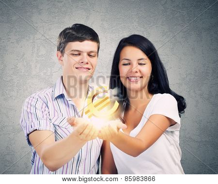 Young happy couple holding euro sign in palms