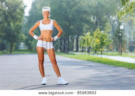 Young attractive sport girl in white sport wear in park