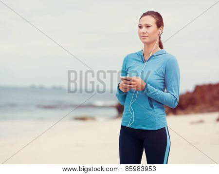 Sporty young woman with earphones on the sea coast