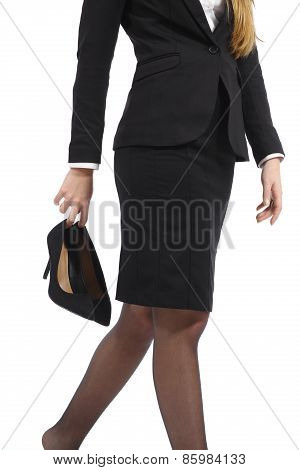 Business Woman Walking Holding Heels In Her Hand