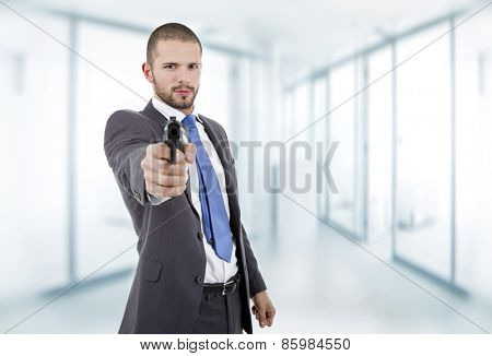 young businessman with a gun, at the office