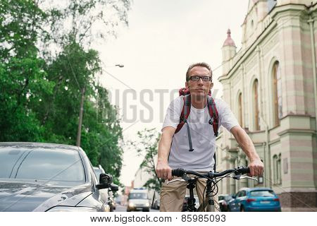 tourist man on a bike at city street